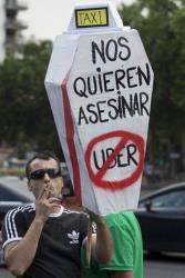 A demonstrator carries a mock coffin with a message reading 'They want to kill us - Uber' during a taxi protest in Madrid Wednesday.