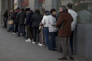 People wait in line to enter an unemployment registry office in Madrid, Spain.