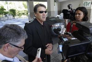 Texas Gov. Rick Perry, center, talks to reporters in Sacramento, Calif., Tuesday, June 10, 2014.