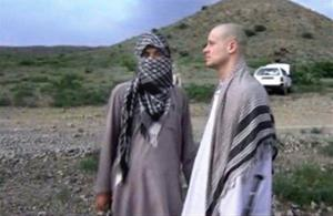 In this file image taken from video, Bowe Bergdahl, right, stands with a Taliban fighter in eastern Afghanistan before his release.