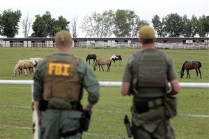 In this June 12, 2012 file photo, FBI agents overlook a horse ranch under investigation in Lexington, Okla.