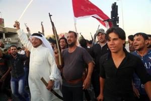 Shiite tribal fighters raise their weapons and chant slogans in Basra, Iraq's second-largest city, 340 miles southeast of Baghdad, Iraq, Sunday, June 15, 2014.