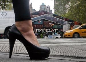 A high-heeled woman stands across the street from the tents in Bryant Park on the last day of New York Fashion Week, Thursday, Sept. 17, 2009.