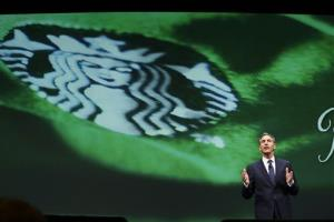 Howard Schultz, chairman and CEO of Starbucks Coffee Company, speaks in front of an image of the Starbucks logo.