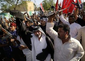 Shiite tribal fighters raise their weapons and chant slogans against Sunni militants, in Basra, Iraq's second-largest city, 340 miles southeast of Baghdad, Iraq, Monday, June 16, 2014.