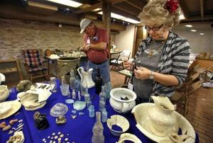 Paul and Synthia DeBarthe stand amongst some of the artifacts dug up at the Joseph Smith Historic Site.