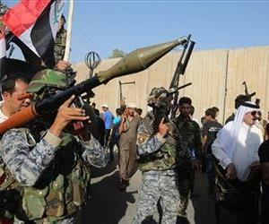 Shiite tribal fighters raise their weapons and chant slogans against the Islamic State of Iraq and the Levant (ISIL) in the northwest Baghdad's Shula neighborhood, Iraq, Monday, June 16, 2014.