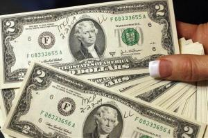 A Medical Center Pharmacy employee gets a handful of $2 bills in 2009 in Brewton, Ala., after her employer paid bonuses the same way.