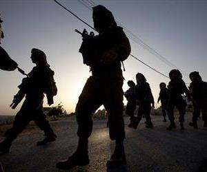 Israeli soldiers patrol during a military operation to search for three missing teenagers outside the West Bank city of Hebron, Monday, June 16, 2014.