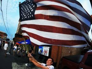 A soccer fan waves a flag outside of a bar in downtown Scranton, Pa., after the United States defeated Ghana 2-1.