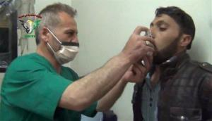In this image taken from video posted on April 18, 2014, a Syrian man is treated with an inhaler in Kfar Zeita, a rebel-held village in Hama province.