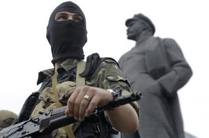 A pro-Russian fighter looks on in Donetsk, eastern Ukraine Saturday, June 21, 2014, with a statue of Soviet Union founder Vladimir Lenin on the right.