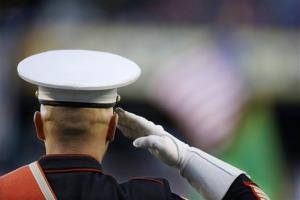 A US Marine from the 1st Marine Division Band salutes as the band plays the national anthem before a baseball game between the Seattle Mariners and Texas Rangers Friday, April 25, 2014, in Seattle.