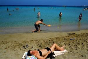 Tourist and Cypriots enjoy the sea and sun at Konnos beach near the famous coastal resort of Ayia Napa, Cyprus, Sunday, May 25, 2014.