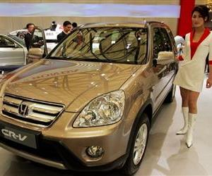In this April 21, 2005 file photo, a model poses by a Honda's CR-V at Auto Shanghai 2005 exhibition in Shanghai, China.