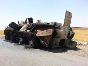 A burned Iraqi Army armored vehicle sits outside Baiji refinery.