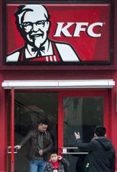 A Chinese man and a child exit a KFC restaurant in Beijing Monday, Feb. 25, 2013.
