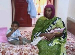 In a June 5, 2014, photo from Al Fajer, a Sudan NGO, Meriam Ibrahim sits next to her son and holds the daughter she gave birth to in jail, as the NGO visits her in a room at a prison in Khartoum.
