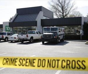 Investigators work the scene of an armored car robbery at a TD Bank branch on Thursday, April 17, 2014, in Philadelphia.