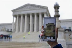 A Supreme Court visitor takes pictures with her cell phone outside the Supreme Court Tuesday.