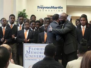 Tracy Martin, right, the father of Trayvon Martin, hugs Florida Memorial University's director of student activities before speaking at a ceremony to open the Trayvon Martin Foundation offices.