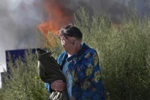 A woman cries near her burning house after shelling in the city of Slovyansk, Donetsk Region, eastern Ukraine, Monday, June 30, 2014.