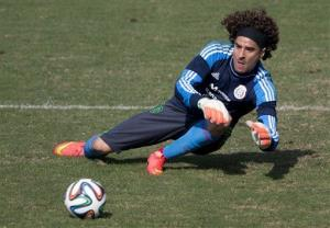 Mexico goalkeeper Guillermo Ochoa leaps to trap a ball during a training session in Santos, Brazil, Thursday, June 26, 2014.