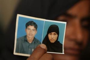 Nargas Bibi shows family pictures of her son Sajjad Ahmed and his wife Muafia Bibi, who were killed by Bibi's parents.