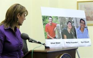 Leehy Shaer, the aunt of kidnapped Israeli-American teen Naftali Frenkel, looks at a photo of the three missing teens during a news conference in Washington.