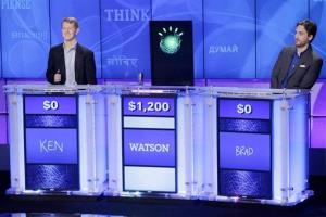 A prop representing Watson is seen with vanquished human opponents during a Jeopardy practice round.