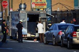 Investigators work at the scene of a food truck explosion in Philadelphia's Fentonville neighborhood.