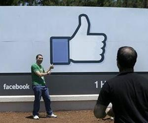 In this June 11, 2014 photo, a man poses for photographs in front of the Facebook sign on the Facebook campus in Menlo Park, Calif.