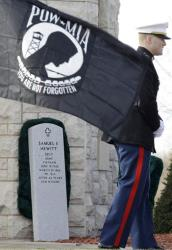 The gravestone of U.S. Marine Staff Sgt. Samuel Hewitt rests against a wall as a POW-MIA flag blows in the wind at the Ohio Western Reserve National Cemetery, Friday, Nov. 19, 2010, in Rittman, Ohio.
