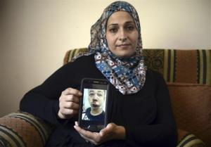 Suha Abu Khdeir, mother of 15-year-old Tariq Abu Khdeir, a U.S. citizen who goes to school in Tampa, Florida, sits in her home and shows a tablet with a photo of Tariq taken in a hospital after he was beaten and arrested by the Israeli police during clashes sparked...