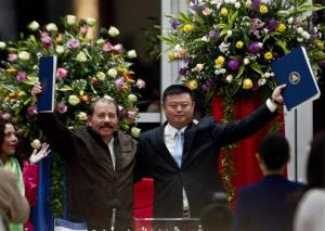 In this June 14, 2013 file photo, President Daniel Ortega and Chinese businessman Wang Jing hold a deal for a multibillion-dollar canal. Nicaragua and China's HKND Group unveiled the route yesterday.