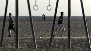 Joggers are seen through public exercise equipment on Santa Monica Beach, in Santa Monica, Calif.
