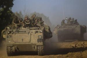 Israeli soldiers drive an armored personnel carrier to a position near the Gaza border today.