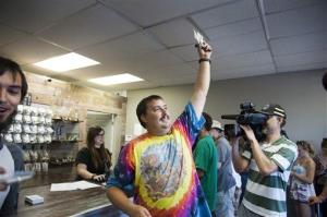 Mike Boyer turns to the crowd outside, showing off the 4 grams of marijuana he bought as the first in line to legally purchase marijuana at Spokane Green Leaf, July 8, 2014, in Spokane, Wash.