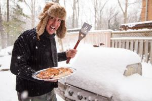 A man in a scarf and fur hat goes out in the snow to light his barbecue.
