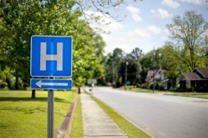 In this April 25, 2014 photo, a sign points the way to Flint River Hospital which closed its emergency room last year, in Montezuma, Ga.