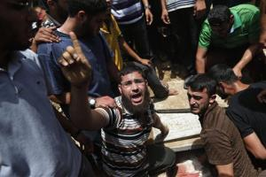 A Palestinian mourner chants slogans on the grave of a member of the al-Batsh family who were killed in Saturday's Israeli airstrike, during a funeral procession in Gaza City on Sunday, July 13, 2014.