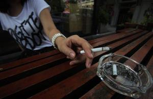 A woman smokes a cigarette outside of a restaurant in this file photo.