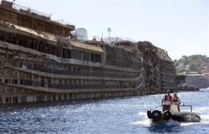 A small boat passes next to the damaged side of the Costa Concordia  on the Tuscan Island of Giglio, Italy.