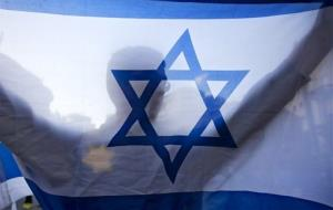 A right-wing Israeli holds a flag and wears a Star of David patch resembling the one Jews were forced to wear in Nazi Germany during a demonstration in Jerusalem, Monday, July 14, 2014.