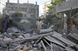 A Palestinian man inspects the rubble from a damaged house this morning following an overnight Israeli missile strike in Gaza City.