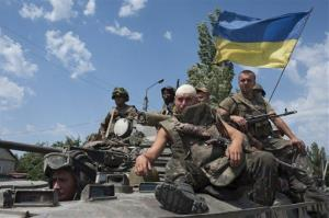Ukrainian government soldiers drive atop an armored vehicle with a Ukrainian national flag outside the city of Siversk, Donetsk region, eastern Ukraine, Saturday, July 12, 2014.