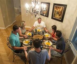 Bob Mueller, 60, center background, leads his family in a prayer before they eat in the home they live in as home managers for Showhomes in Tampa, Fla. on Tuesday, July 1, 2014.