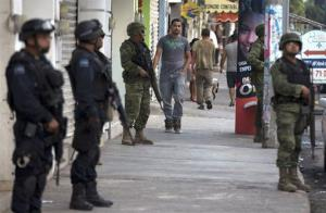 Federal police and soldiers stand guard in Apatzingan, Mexico, in this file photo.