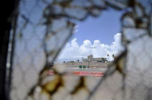 In this Aug. 23, 2013 pool file photo reviewed by the US Department of Defense, one of Guantanamo Bay's two courthouses is seen through a broken window.