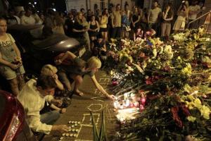 People hold candles and place flower tributes outside the Dutch embassy in Kiev to commemorate victims of the Malaysia Airlines plane crash.